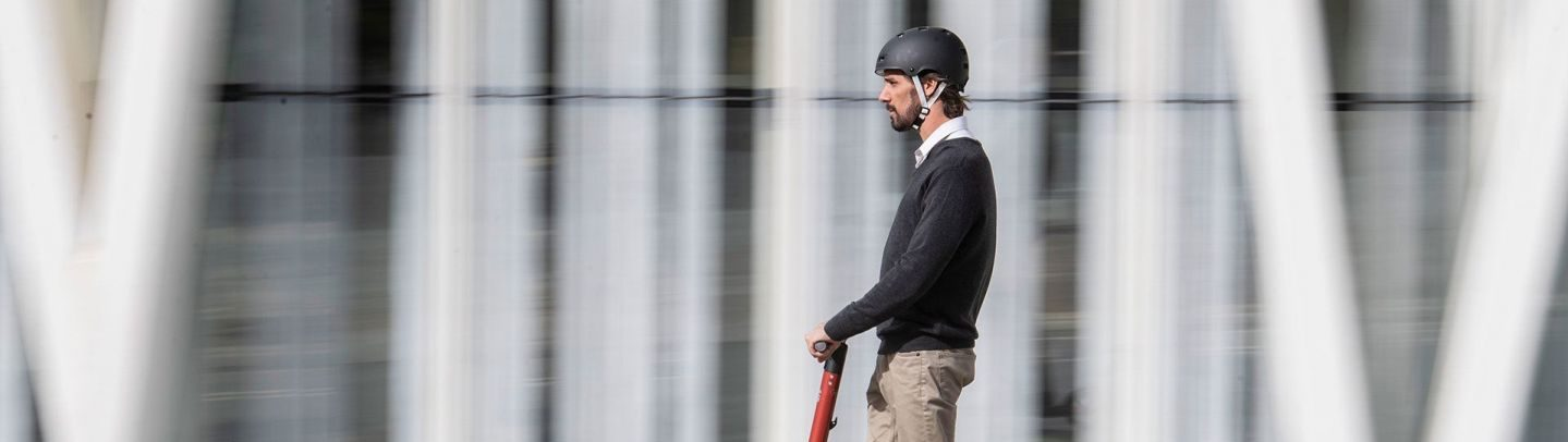 hombre circulando con casco homologado sobre patinete electrico